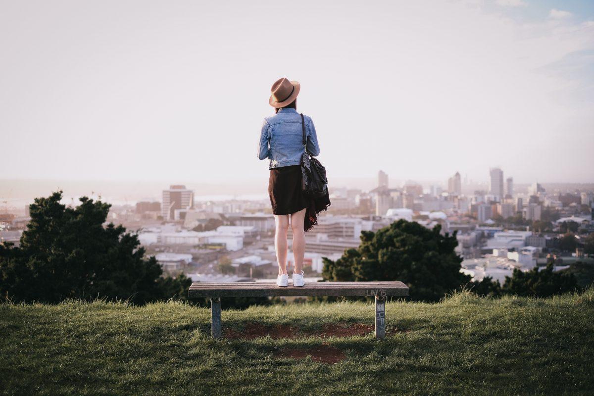 Frau steht auf einer Bank und blickt auf die Stadt